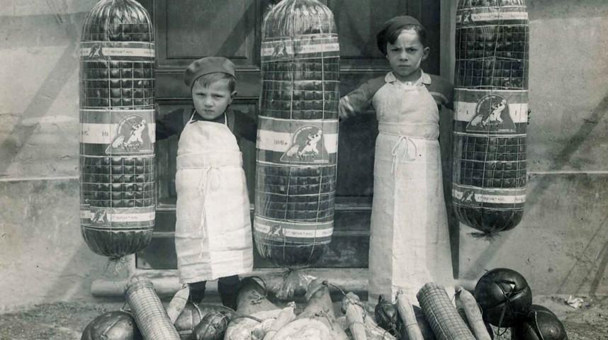 Sulla destra Ezio Veroni con il cugino Giulio, presidente dell'azienda fino al 2007. Questa foto fu scattata nei primi anni '30, e già la produzione Veroni era caratterizzata da mortadelle di grandi dimensioni.