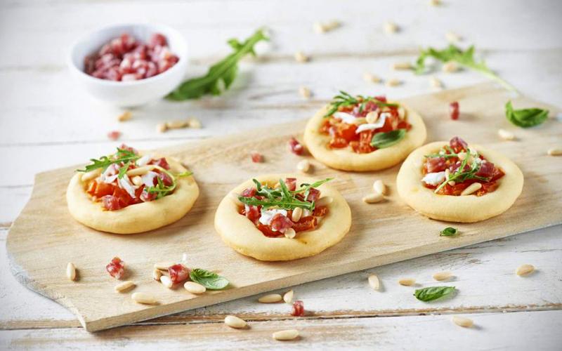 Pizzette al salame con pinoli, pomodoro fresco, burrata e rucola