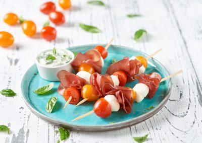 Spiedini di bresaola, mozzarelline e ciliegini bicolor con crema di basilico senza aglio e formaggio cremoso